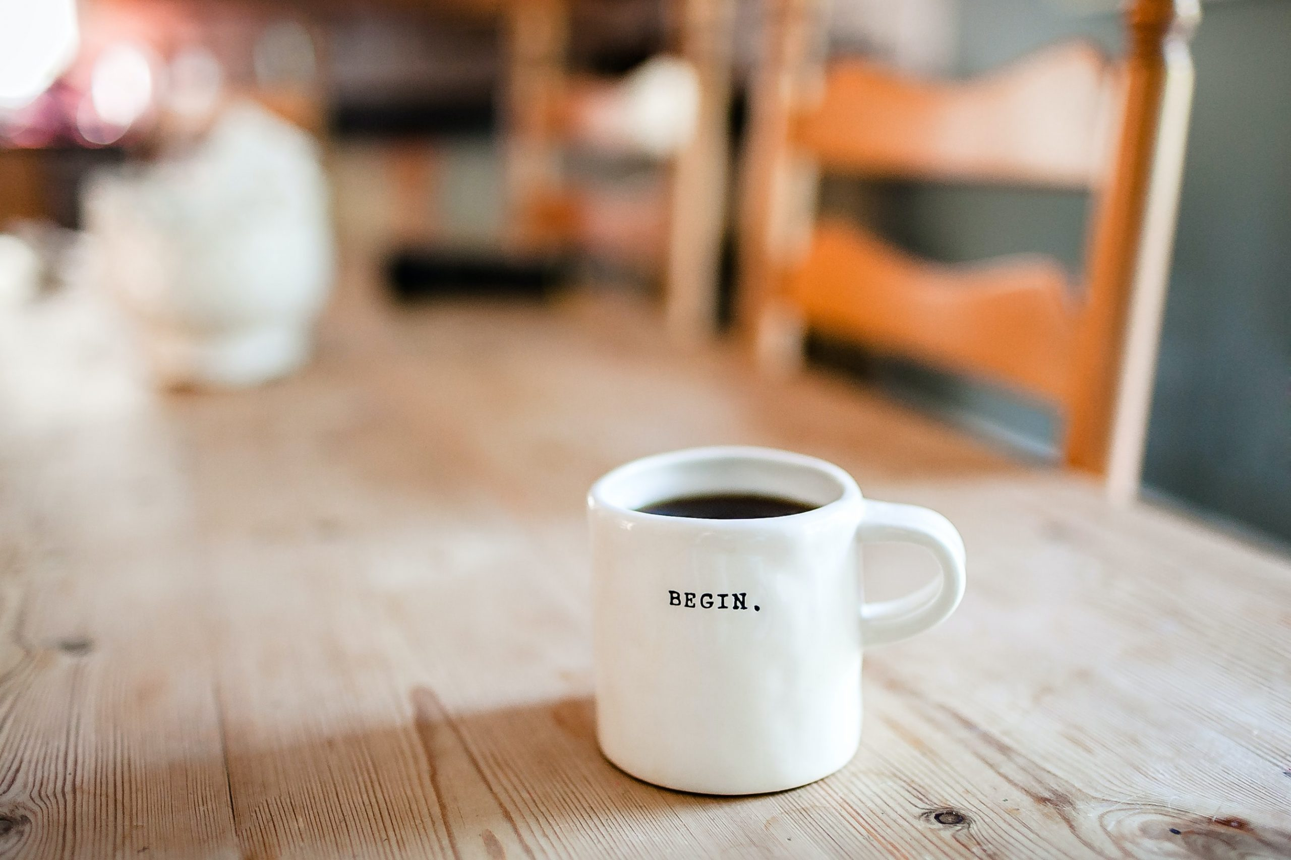 Coffee cup on table with word begin